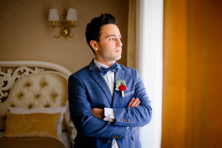 Handsome groom crosses his hands on the chest while looking through the window