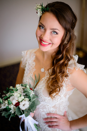 Happy bride with beautiful blue eyes poses in rich hotel room Stock Photo