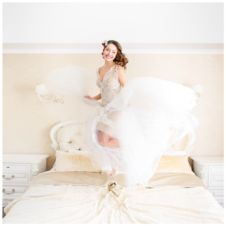 Happy bride with dark blonde hair jumps on the bed
