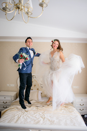 Happy newlyweds jump on bed in hotel room