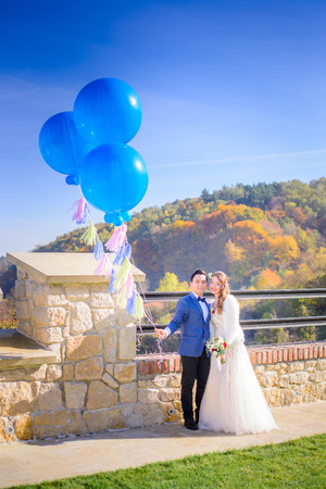 Happy newlyweds hold  blue big balloons while posing before autumn mountain landscape