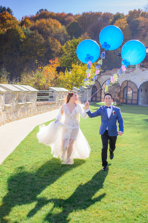 Cheerful wedding couple runs along the lawn with blue balloons