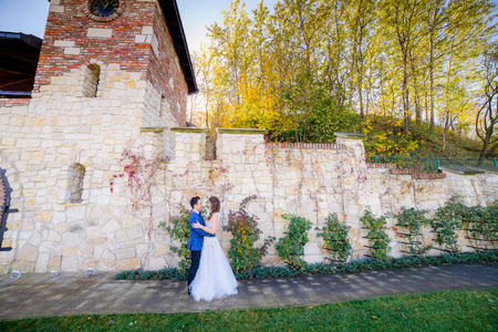 Stylish wedding couple poses before old white fortress