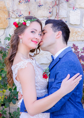 Handsome groom in blue jacket kisses tender brides neck while she smiles