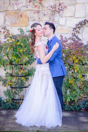 Bride in red flower wreathe stands in groom's hugs
