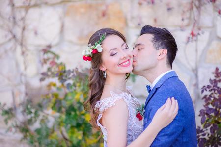 Stunning bride smiles holding her hands on groom's blue jacket