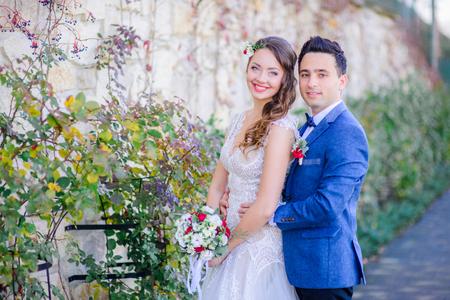 Brunette groom hugs his tender bride from behind while posing before white wall in green ivy