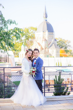 Blessed wedding couple pose on the bridge before old cathedral