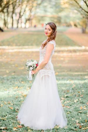 Delightful bride stands on fallen leaves in autumn park Stockfoto