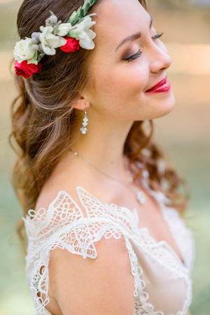 Comely bride in red wreathe closes her eyes standing outside
