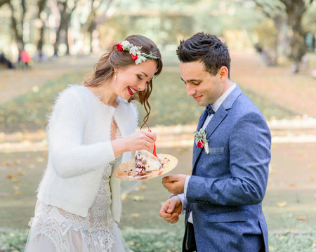 Bride in fluffy jacket smiles while holding before a groom a piece of wedding cake