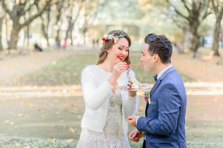 Groom in blue jacket kisses wedding cake from bride's hands while standing outside Stockfoto