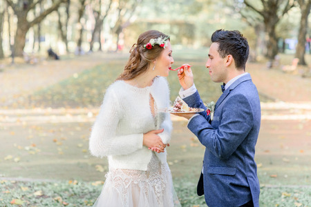 Pretty bride in red wreahe kisses wedding cake from groom's hand