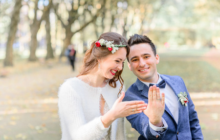 Laughing newlyweds show wedding rings on their hands