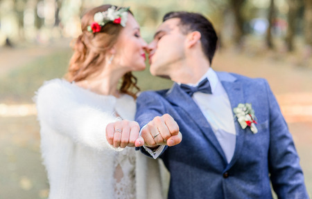 Kissing newlyweds reach out their fists with wedding rings
