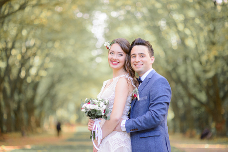 Fabulous wedding couple stands in green and yellow autumn park