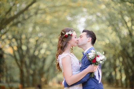 Angelic bride and groom kiss hugging each other tightly