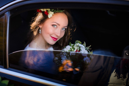 Look through the cars window at wonderful bride sitting inside
