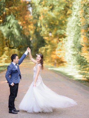 Stylish groom in blue jacket whirls happy bride in autumn park