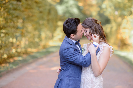 Handsome brunette groom touches bride's face while they pose in park Banque d'images