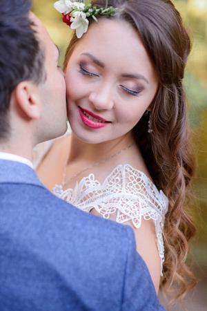 Radiant bride closes her eyes while groom kisses her cheek tender