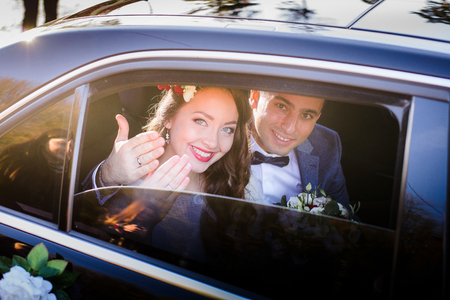 Happy newlyweds show their hands with wedding rings through car's window Stockfoto