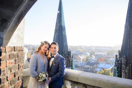 Attractive groom and bride in grey jacket stand on the balcony with great view on the city