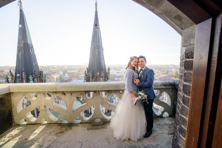 Groom holds tender bride's hands while they stand on old white balcony