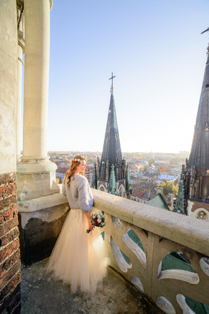 Sun shines over gorgeous bride while she admires city from the balcony