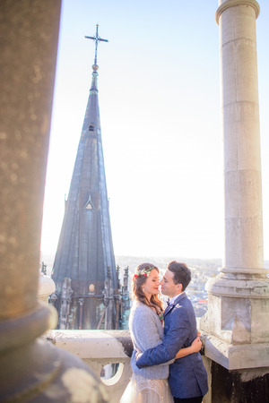 Bright sun shines over wedding couple kissing between the white pillars on balcony