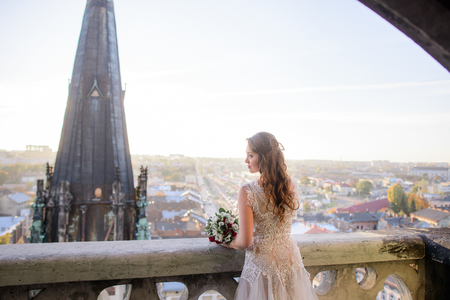 Lonely woman with long curls bends over the balcony while looking at gorgeous city