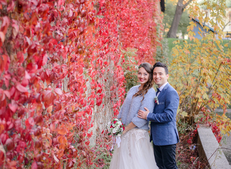 Luxuriant wedding couple hugs before wall in red ivy