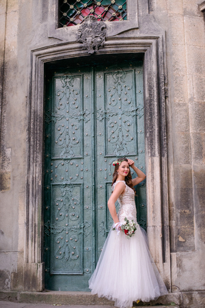 Chic bride poses before old green door