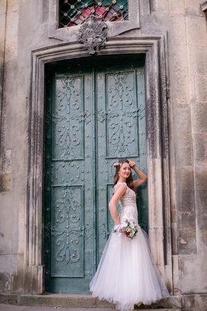 Chic bride poses before old green door