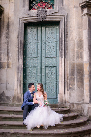 Bride and groom in blue suit rest on the old stone footsteps