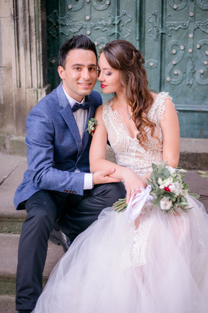 Tender bride lies her hand over groom's knee while they rest on footsteps Stockfoto