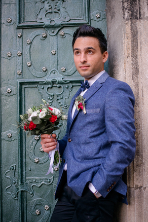 Handsome brunette groom stands with red bouquet before green door Zdjęcie Seryjne