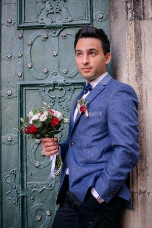 Handsome brunette groom stands with red bouquet before green door Stockfoto