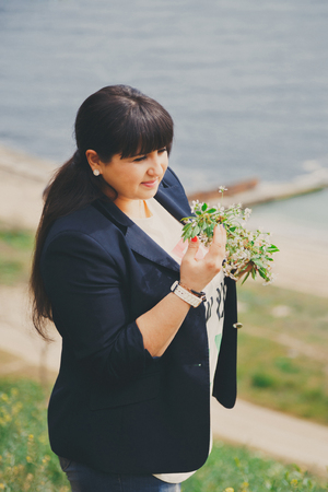 Happy smiling beautiful overweight young woman in dark blue jacket outdoors near to the sea with flowers. Confident fat young woman. Xxl woman, plus size woman on nature