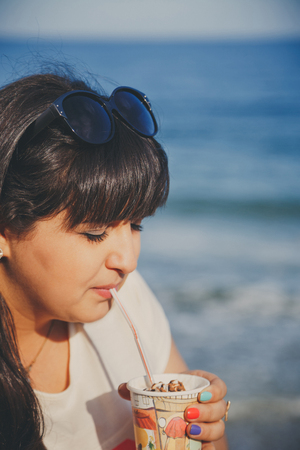 Portrait of happy smiling beautiful overweight young woman in white T-shirt drinking sweet coffee through a straw outdoors at beach. Confident fat young woman. Xxl woman, plus size woman Stock Photo