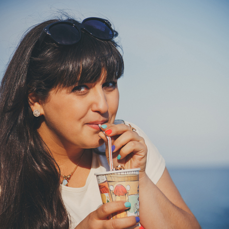 oversized: Portrait of happy smiling beautiful overweight young woman in white T-shirt drinking sweet coffee through a straw outdoors at beach. Confident fat young woman. Xxl woman, plus size woman Stock Photo