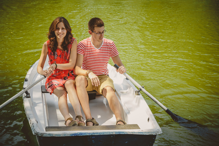 Young beautiful happy loving couple rowing a small boat on a lake. A fun date in nature. Couple hugging in a boat
