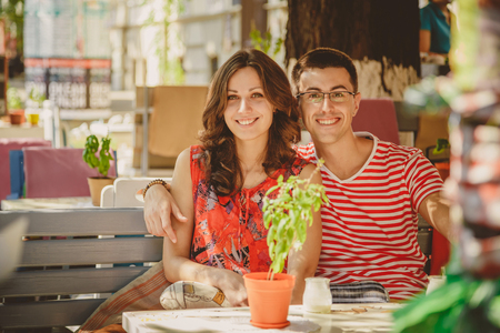 touching noses: Young beautiful happy loving couple sitting at street open-air cafe, hugging. Beginning of love story. Relationship love, lifestyle concept. Couple in love on a date Stock Photo