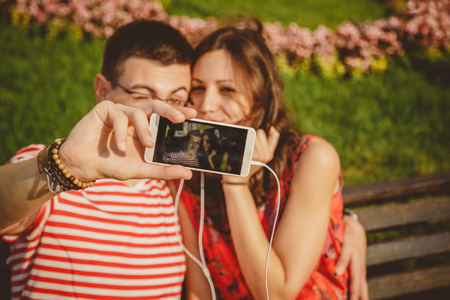 Happy young couple having fun at park and taking selfie enjoying sunny day outside.
