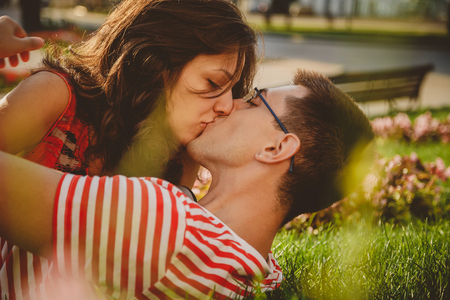 close up of lovely couple lying on green grass in park kissing