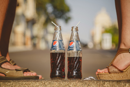 ODESSA, UKRAINE - OCTOBER 15, 2014: Close up of woman feet standing on tiptoe while kissing with man outdoors summertime. Pepsi in glass bottles with straw is standing between a couple.
