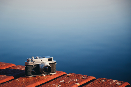 lake front: Old vintage film photo camera lying on wooden berth, dark blue water background. Copy space.