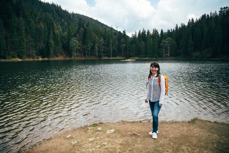 surrounded: Young woman, tourist with orange backpack standing on the bank of the big mountain lake surrounded by forest. Travel destination concept Stock Photo