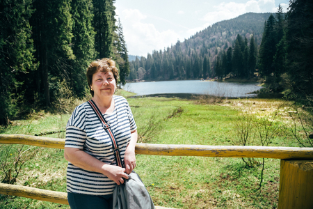 surrounded: Tourist aged beautiful woman standing on the bank of the mountain lake surrounded by forest, enjoying silence and harmony of nature Stock Photo