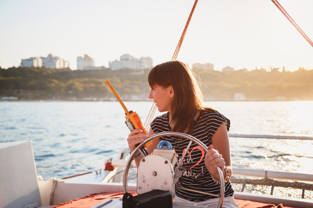 Young pretty smiling girl in striped shirt and white shorts driving luxury yacht with walkie-talkie in hands, hot summer day, sunset